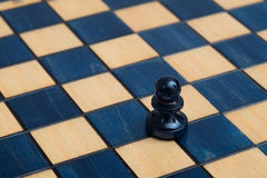 Dark blue pawn on wooden chessboard Royalty Free Stock Images