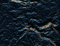 Dark blue perforated rough surface with cracks and golden inclusions, stone. Dark background