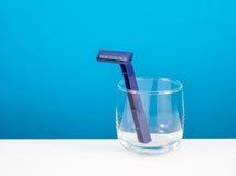 The dark blue plastic razor and round glass Stock Photos