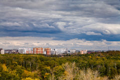 Dark blue rainy clouds over city in autumn. Dark blue storm clouds over city and urban park in autumn stock photography