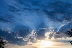 Dark blue rainy clouds over sundown sun Royalty Free Stock Image