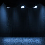 Dark blue scene interior with spotlights. Wooden stage and fabric background Royalty Free Stock Photo