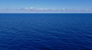 Dark blue sea with clouds and sky on the horizon. Very calm dark blue ocean with some clouds and light blue sky on the horizon stock images