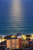 Moonshine on dark-blue sea at seaside resort. Aerial image of the dark-blue sea glimmering by full moon at the lighted beach of Surfers Paradise, Gold Coast royalty free stock photography