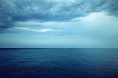 Dark blue sea and stormy clouds Stock Images