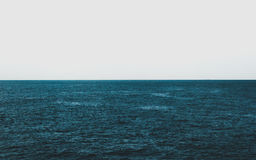 Dark blue sea and white sky Royalty Free Stock Images