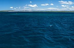 Dark blue seawater surface and distant coastline. Surface of blue, rippled sea water and distant coastline and cloudy sky, Adriatic Sea, Croatia Stock Photo