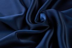 Dark blue silk fabric background, view from above. Smooth elegant blue silk or satin luxury cloth texture can use as abstract background with copy space, close royalty free stock photos