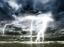 Dark blue sky. Beautiful bright lightning strikes from the dark blue sky into the ocean Stock Photo