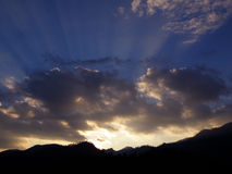 Dark Blue Sky and Gray Cloud Before Sunset over the mountain range Stock Photos