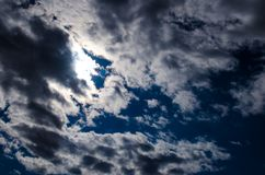 Dark blue sky with a stratocumulus clouds. And the sun behind them Royalty Free Stock Images