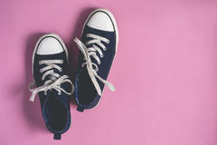 Dark blue Sneakers on pink  pastel background flat lay copy space Royalty Free Stock Images