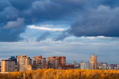 Dark blue snow storm clouds over apartment houses. In city in autumn royalty free stock photo