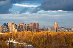 Dark blue snow storm clouds over urban street. And city park in autumn stock photo