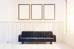 Dark blue sofa in a room with three posters, toned. Dark blue sofa is standing in white room with wooden and concrete walls. There are three vertical framed Stock Photo