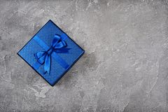 Dark blue square gift box with shiny satin bow. On gray concrete background Royalty Free Stock Photo