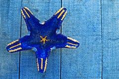 Dark blue starfish shape on blue decking Royalty Free Stock Photos