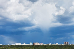 Dark blue storm clouds over city in summer Stock Photo