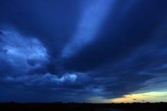 Dark blue storm clouds at sunset Stock Photos