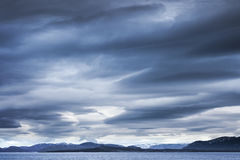 Dark blue stormy clouds over the mountains. Empty Norwegian sea landscape Royalty Free Stock Images