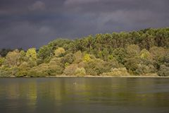 Dark blue stormy sky over river and forest. Nature before storm. Beautiful river landscape. Meteorology and weather concept. Dark blue stormy sky over river and royalty free stock image