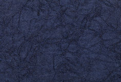 Dark blue wavy background from a textile material. Fabric with natural texture closeup. Stock Photo