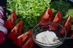 On a dark board lie oats sliced ​​for salad. Tomatoes, radishes, cabbage, dill, celery, parsley, also stand in a transparent bowl sauce. Near royalty free stock photography