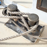 Dark bollard with rope on yacht deck Stock Image