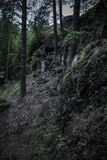 Dark boulders covered in moss on a slope in northern wood. Large stones in the woods awaiting storm stock photo