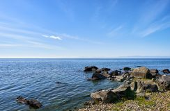 Dark boulders on shore of Lake Baikal. Laconic natural landscape. Irkutsk region. Russia royalty free stock photography