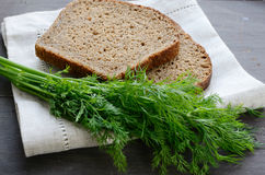 Dark bread and bunch of dill on linen table napkin Stock Images