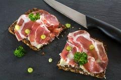 Dark bread with Italian coppa or capicola ham on a dark slate pl Stock Image