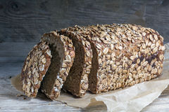 Dark bread loaf with whole grain and seeds on an old wooden boar Stock Image