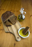 Dark bread, olive oil, and dipping bowl. Royalty Free Stock Images