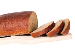 Dark bread with some sliced pieces. Of it placed on isolated background Stock Image