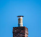 Dark brick chimney and filter on blue sky. Stock Image