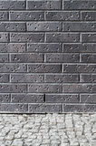 Dark brick wall and grey pebble floor Royalty Free Stock Image
