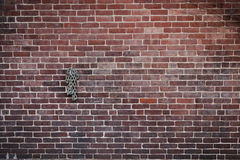 Dark Brick Wall with Rolled Up Chain Hanging. Neat brick wall with light and dark colored bricks as well as a rolled up chain hanging from a spike stock photo