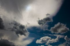 Dark and bright clouds and the sun. Dark and bright clouds of bizarre forms and the sun on the background of a dark blue sky royalty free stock photo