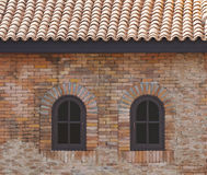 Dark brown arched window in a brick wall Stock Photos