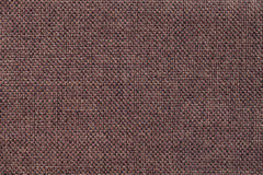 Dark brown background of dense woven bagging fabric, closeup. Structure of the textile macro. Royalty Free Stock Images
