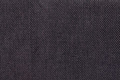 Dark brown background of dense woven bagging fabric, closeup. Structure of the textile macro. Stock Photography