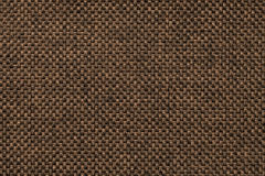 Dark brown background of dense woven bagging fabric, closeup. Structure of the textile macro. Dark brown woolen background of dense woven bagging fabric Stock Images