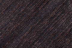 Dark brown background of a knitted textile material. Fabric with a striped texture closeup. Royalty Free Stock Photos