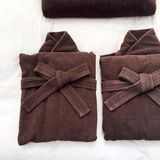 Dark brown bathrobe on bed Stock Photography