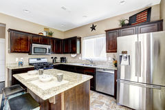 Dark brown cabinets with granite tops. Kitchen room interior. Dark brown cabinets with granite tops. Kitchen island with stools Stock Photo