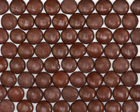 Dark brown dragee in chocolate covered. Stock Photo