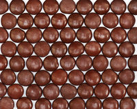 Dark brown dragee in chocolate covered. Whole background stock image