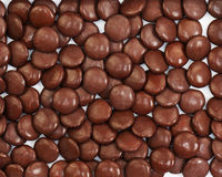 Dark brown dragee in chocolate covered. Whole background royalty free stock image