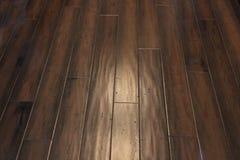 Dark brown hand scraped floor. Dark brown hand scraped engineered hardwood flooring under incandescent lighting royalty free stock photography